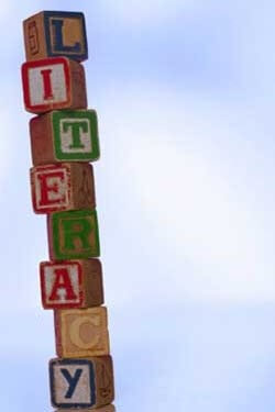 "Photo of a stack of alphabet blocks spelling ""literacy"""