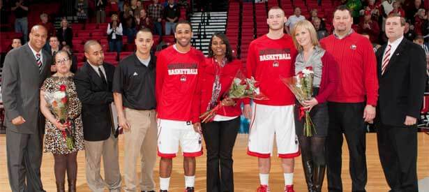 Men's basketball seniors DeMarcus Grady and Tyler Storm pose with their families, Coach Mark Montgomery and Athletics Director Jeff Compher.