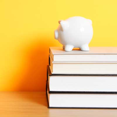 Photo of a piggy bank on a stack of textbooks