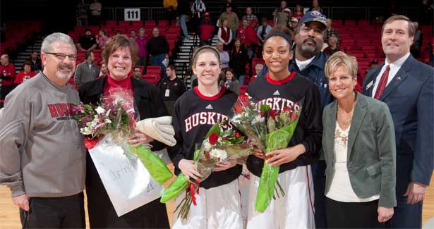 Women's basketball seniors Courtney Shelton and Kim Davis pose with their parents, Coach Kathi Bennett and Athletics Director Jeff Compher on Senior Night.