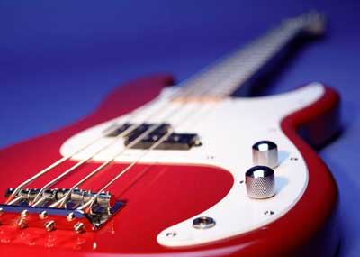 Photo of a red-and-white electric bass guitar
