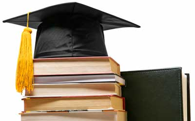 Photo of a graduation cap on a stack of books.