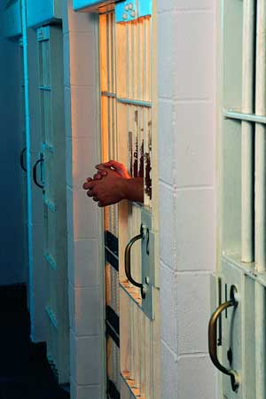 Photo of folded hands inside a jail cell door