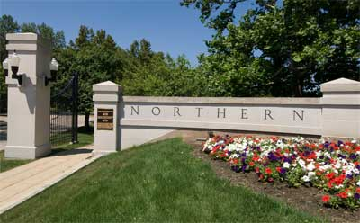 Summertime photo of NIU's front gates on Lincoln Highway