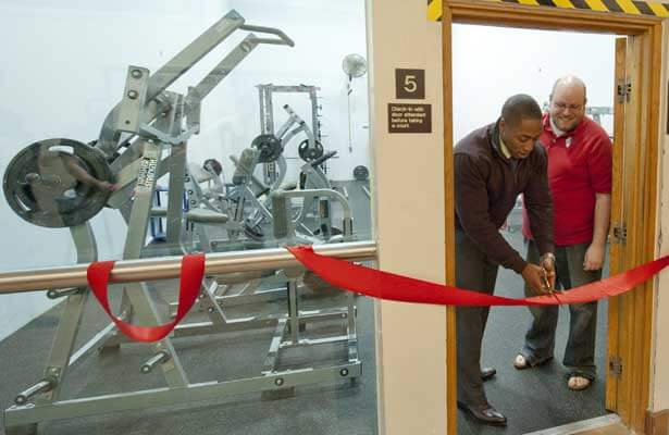Student Association President Elliot Echols cuts the ribbon to the Rec Center Fitness Room as SA Speaker Austin Quick watches.