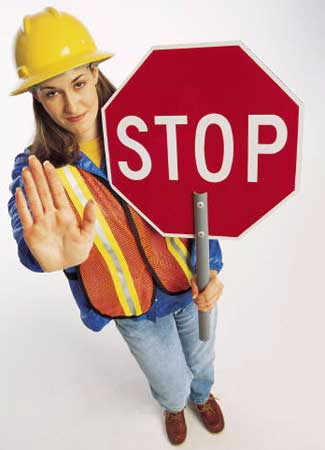 Photo of a road construction crew worker holding a STOP sign