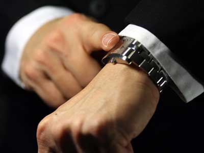 Photo of an man's index finger tapping his wristwatch