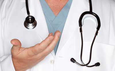 Image of a health care professional with white lab coat, blue scrubs and stethoscope