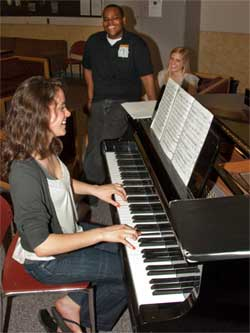 NIU Honors students relax around the piano.