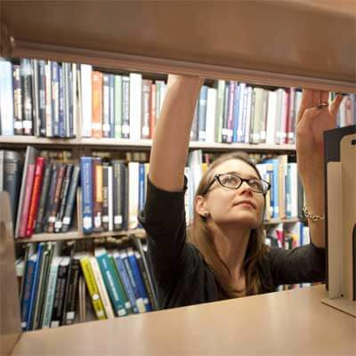 An NIU Honors student looks for a book at Founders Memorial Library.