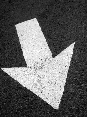 Photo of a down-pointing white arrow painted on black pavement