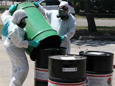 Elicia Bailey and Ryan Sego prepare oil drums for transport