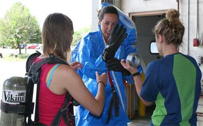 Lauren Schroeder and Briana O'Halleran help Vicky Mikszta prepare to enter a simulated contaminated site.