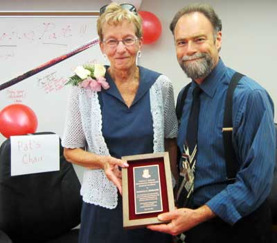 "Steve Cunningham, vice president for Administration and Human Resources, presents Pat Siebrasse with the first ""Patricia S. Siebrasse Administrative Professionals Award for Excellence."" Her beloved chair is on the left."