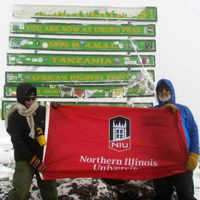Kurt and Jeanine Thurmaier hold their NIU flag at the top of Mt. Kiliminjaro.