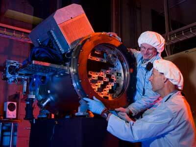 This Fermilab image shows scientists building a prototype of the Dark Energy Camera, which will survey about one-tenth of the sky to measure 300 million galaxies and discover thousands of supernovae.