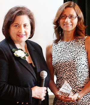 NIU College of Law Dean Jennifer Rosato (right) receives the Impressa award from Phyllis Schoene.