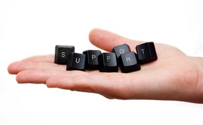 """Photo of a hand holding computer keyboard keys spelling the word """"SUPPORT"""""""