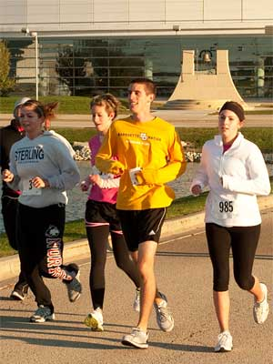 Homecoming 5K runners pass the NIU Convocation Center.