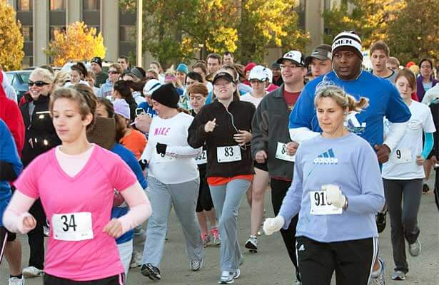 Homecoming 5K runners pass a residence hall.