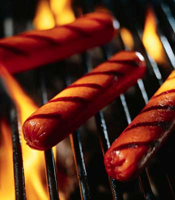 Photo of three hot dogs on a flaming grill