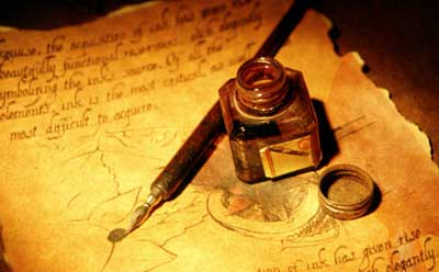 Photo of a bottle of ink and brush on parchment with writing