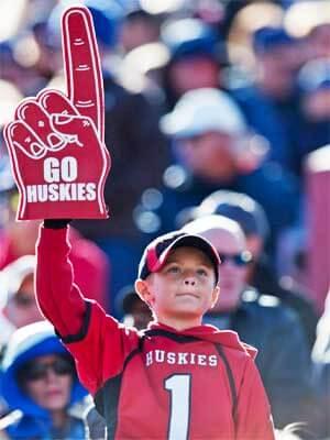 "Photo of a young NIU footbal fan with a ""Go Huskies"" foam finger"