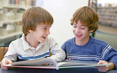 Photo of two boys reading a book in a library