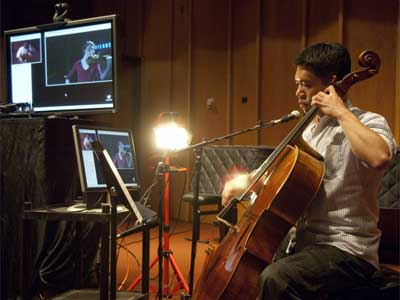 Cheng-Hou Lee performs via Internet2 for an audience in Philadelphia. He can see violinist Marjorie Bagley on the computer monitor.