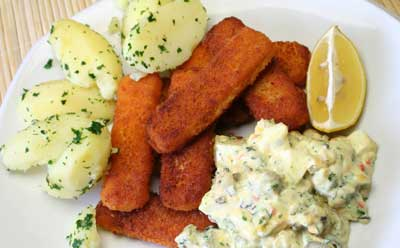 Photo of a dinner plate of fish sticks, potatoes, creamy seafood salad and a lemon wedge