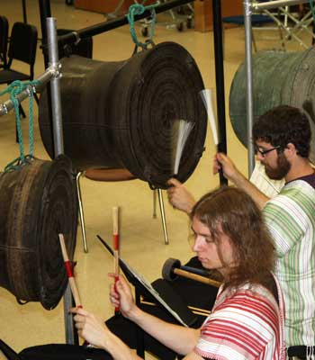 "Students Lane Parsons (left) and Nick Fox rehearse School of Music professor Gregory Beyer's composition ""Five Ponds"" on antique bronze drums from Burma."