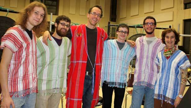 Associate music professor Gregory Beyer, center, and percussion students, from left, Lane Parsons, Nick Fox, Jonny Gifford and Brian Wach take a break from rehearsing to try on traditional Karen tunics from Burma that they will wear when playing Beyer's piece Saturday night during the International Burma Studies Conference. The tunics were provided by Center for Burma Studies Director Catherine Raymond (right).