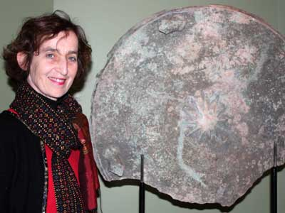 Center for Burma Studies Director Catherine Raymond, organizer of the International Burma Studies Conference at NIU this weekend, shows a fragment of an ancient bronze drum from Burma currently on display at the NIU Art Museum.