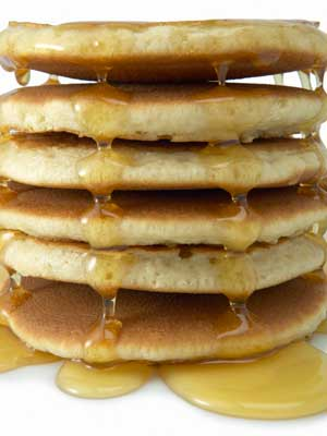 Photo of a stack of pancakes dripping in syrup