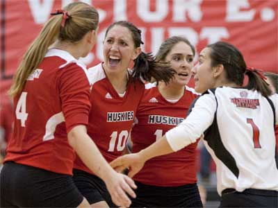 "From left: Meghan Romo, Mary Kurisch, Alexis ""Pookie"" Gonzalez and Justine Schepler celebrate a Huskie volleyball victory."
