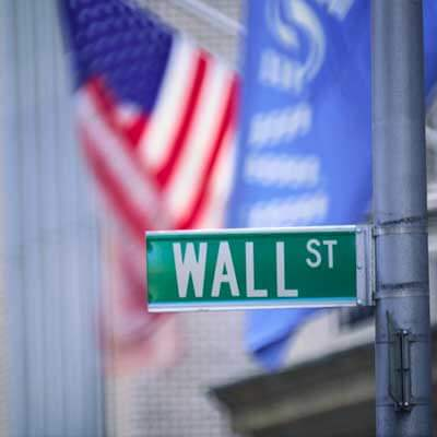 Photo of a Wall Street street sign with a U.S. flag in the background