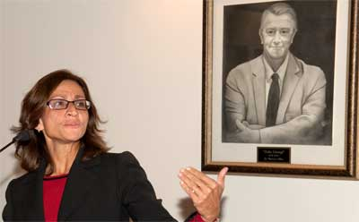 NIU Law Dean Jennifer Rosato speaks at the 10th anniversary of the Zeke Giorgi Legal Clinic. A portrait of the late legendary Rockford lawmaker hangs on the wall behind her.
