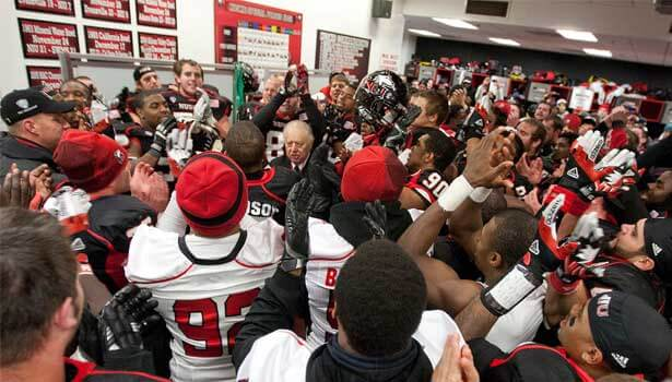 NIU President John Peters celebrates with the football team in the locker room after Wednesday night's 31-24 victory over Toeldo.