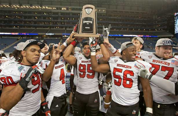NIU Huskie football players hoist the MAC championship trophy