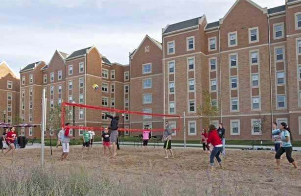 Students play volleyball on the sand court outside the New Residence Hall.