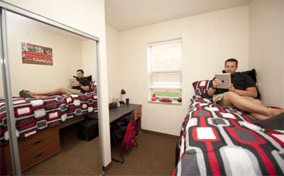 An NIU student relaxes in his room in the New Residence Hall.
