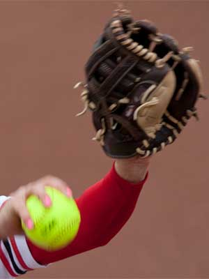 Photo of a NIU softball pitcher's arm and hand with ball and glove