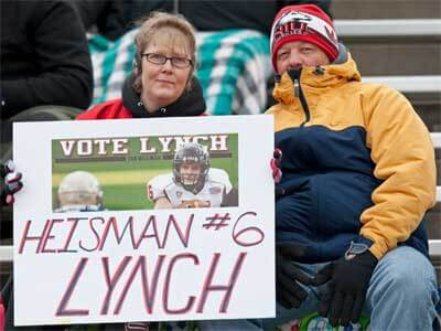 """Photo of two NIU football fans with a """"HEISMAN #6 LYNCH"""" sign"""
