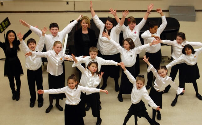 The CSA Children's Choir poses for a photograph with Mary Lynn Doherty, center, minutes before performing at the winter concert at NIU on Dec. 12.