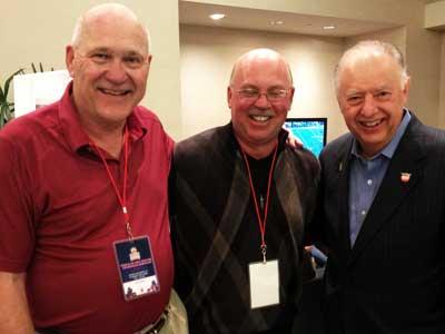 Former NIU football coaches Joe Novak and Jerry Kill visit with President John Peters in Miami.