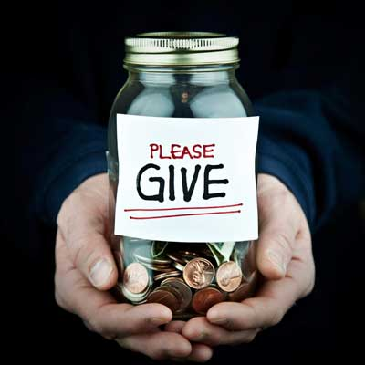 "Photo of hands holding a glass jar of coins with a ""Please Give"" label"