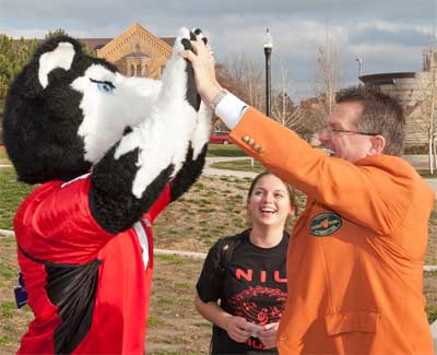 Victor E. Huskie high-fives Larry Gautier, a member of the football committee for the Discover Orange Bowl.