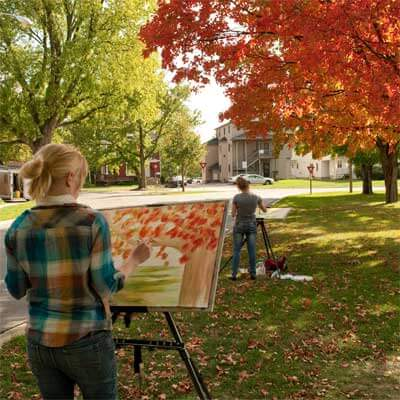 NIU art students paint outside the Music Building during class.