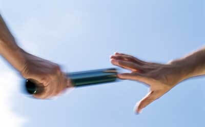 Photo of one hand passing the baton to the next