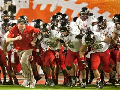 Coach Rod Carey leads the NIU Huskies onto the field at the 2013 Orange Bowl.